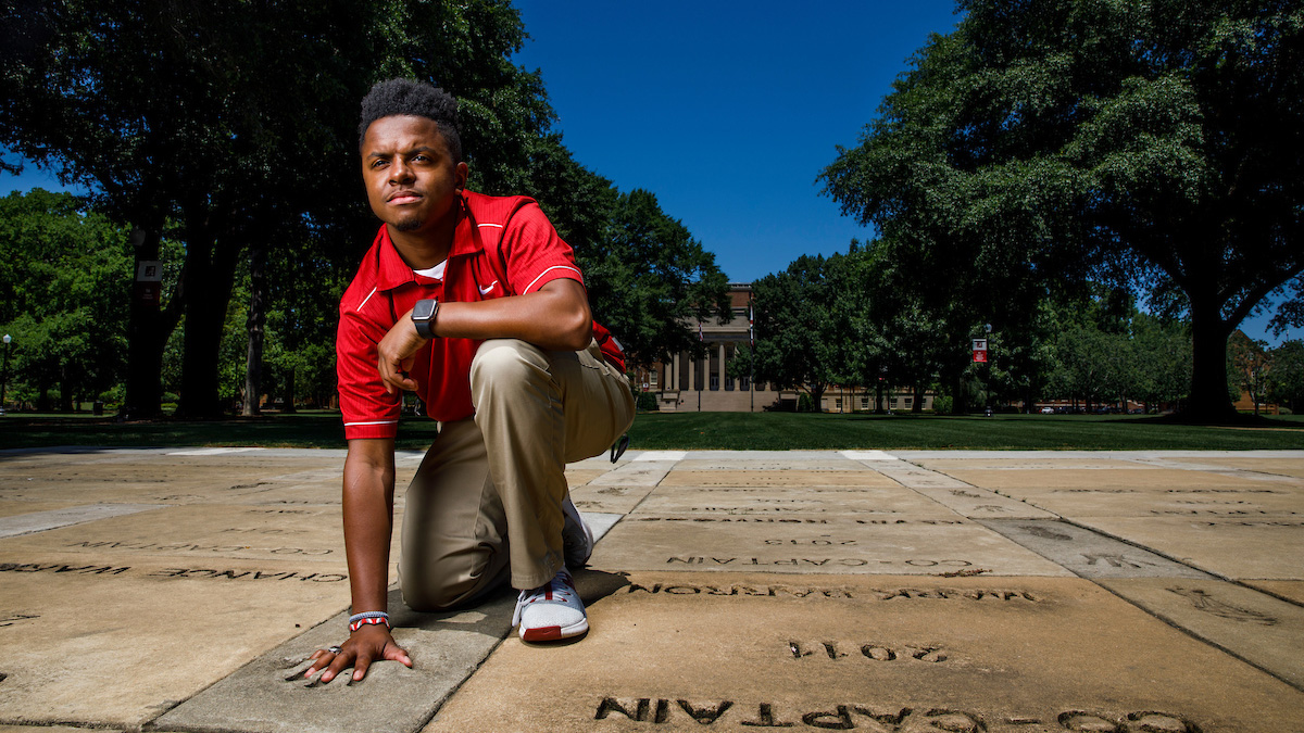 Student with hand in handprint at Walk of Champions