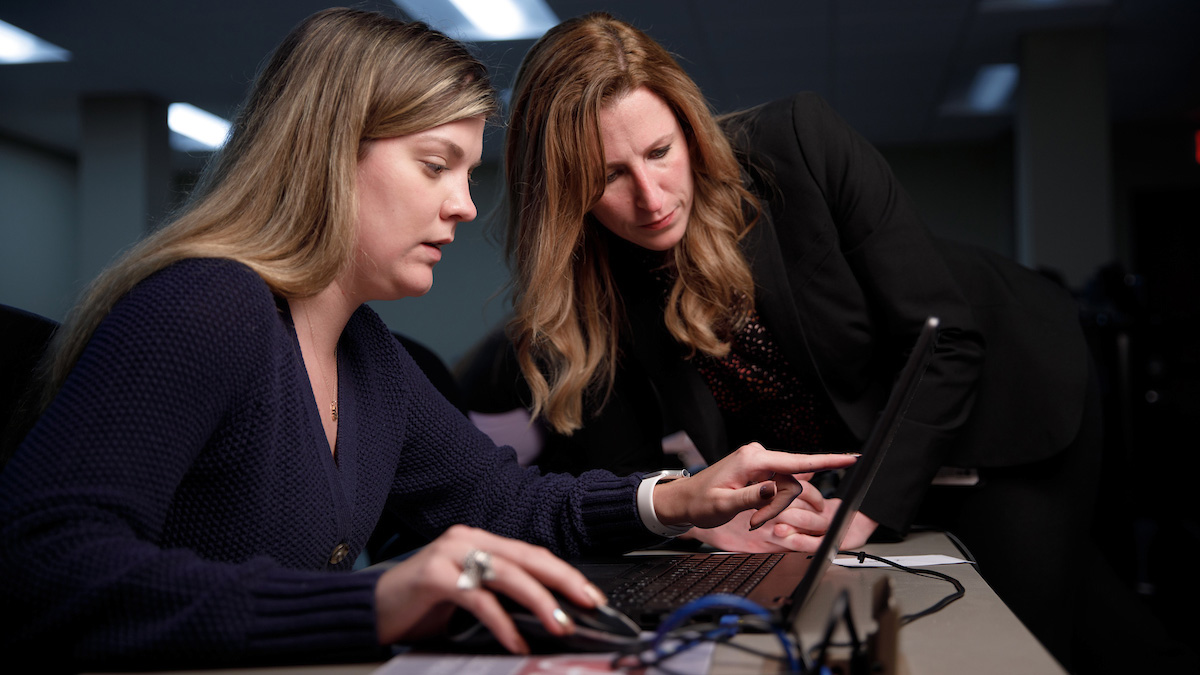 Professor helping student at her computer