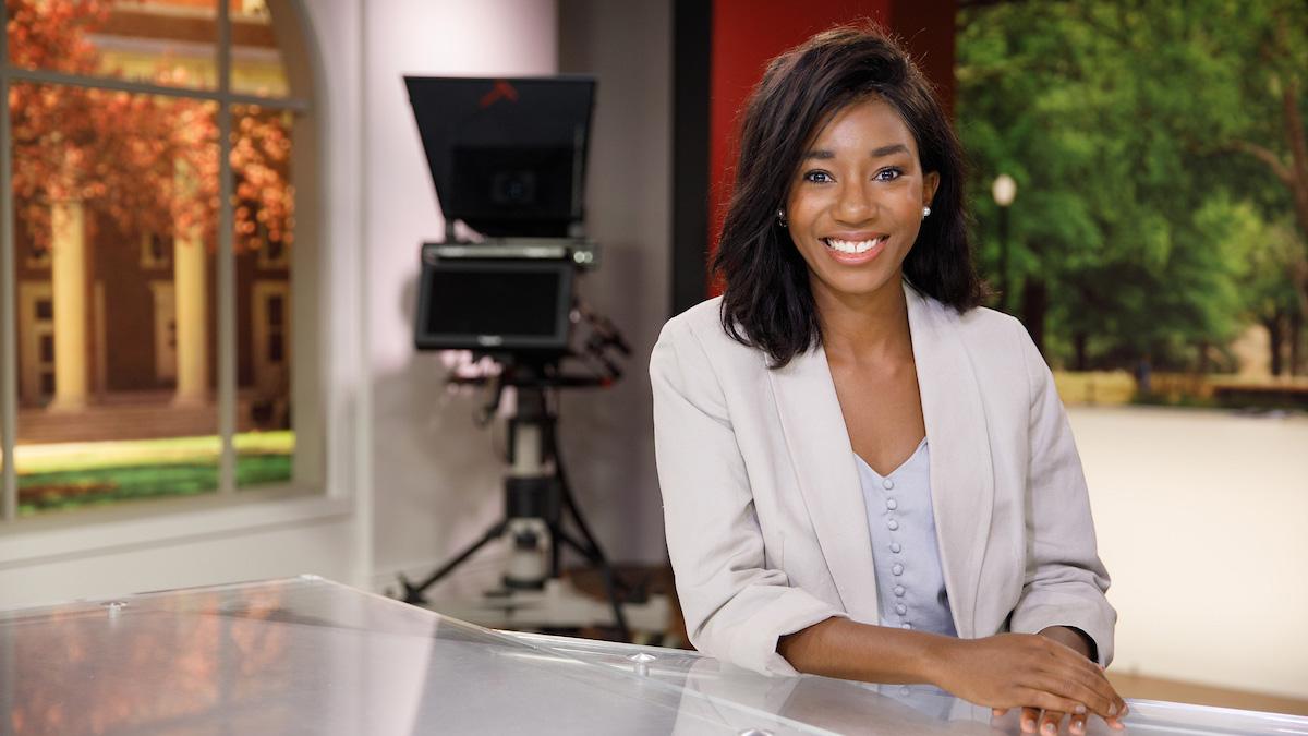 Student sitting at news desk on WVUA TV set