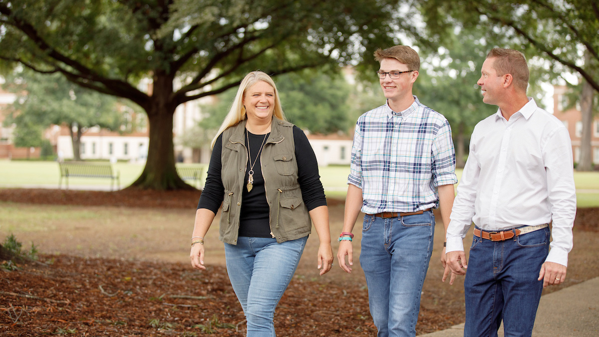 Student walking with his parents on the Quad