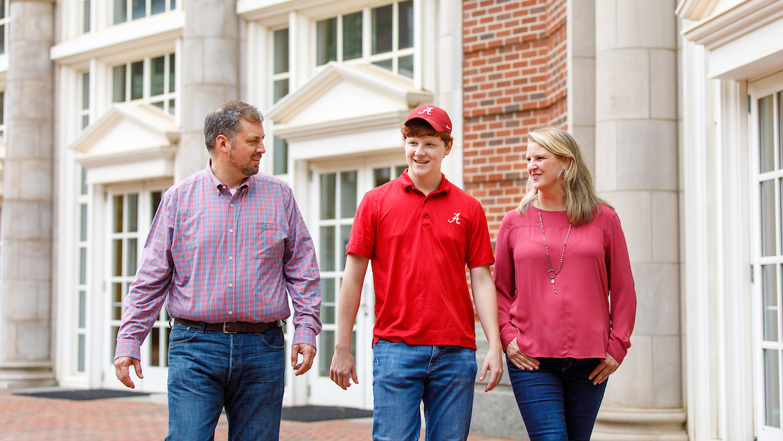 Student walking with his parents outside Shelby Hall