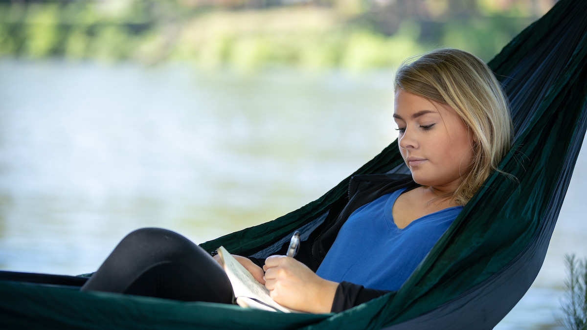 Student writing in a hammock on the riverwalk